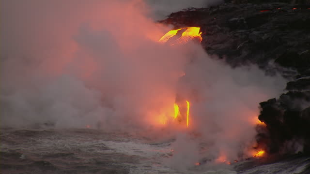 molten lava flowing into the sea in hawaii volcanoes national park. - vulkanausbruch stock-videos und b-roll-filmmaterial