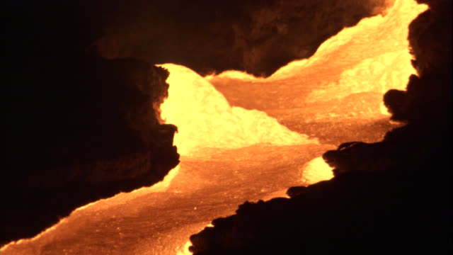 molten lava flows through a silhouetted channel. available in hd. - lava stock videos & royalty-free footage
