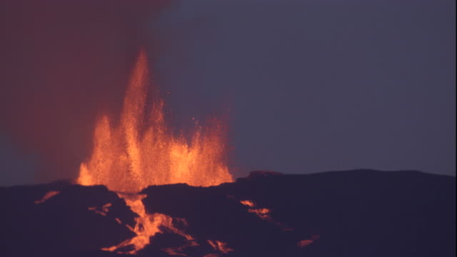 Molten lava from a volcanic eruption spews into the sky. Available in HD.