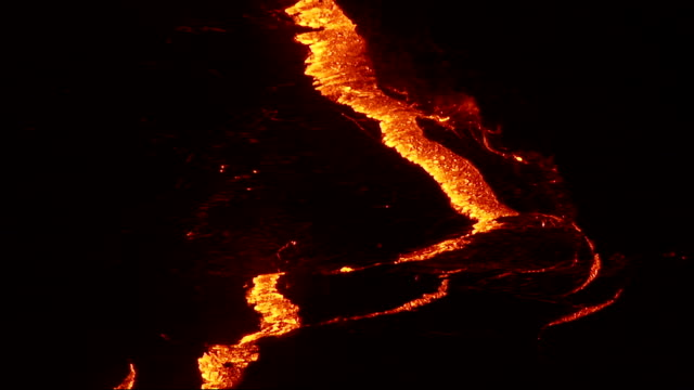 Molten lava splits through the thin surface of volcano crust. Available in HD.