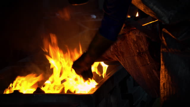 molten metal melting, operator tapping molten metal from furnace to ladle for pouring to in foundry factory - furnace stock videos & royalty-free footage