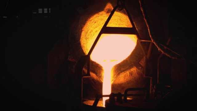 molten metal melting, operator work hard tapping molten metal from furnace to ladle for pouring to in foundry factory - molten stock videos & royalty-free footage
