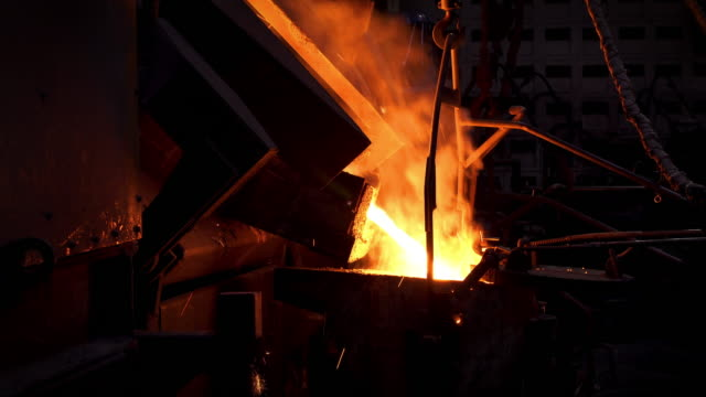 molten metal melting, operator work hard tapping molten metal from furnace to ladle for pouring to in foundry factory - conveyor belt stock videos & royalty-free footage