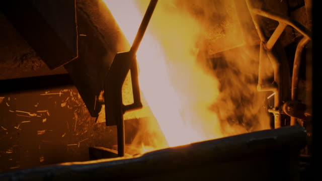 molten metal melting, operator work hard tapping molten metal from furnace to ladle for pouring to in foundry factory - metal industry stock videos & royalty-free footage