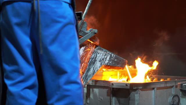vidéos et rushes de fusion des métaux fondus, l'opérateur travaille dur en tapant le métal fondu du four à la louche pour verser dans l'usine de fonderie - acier