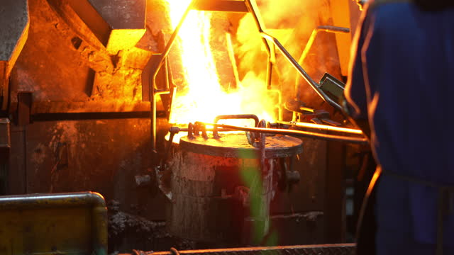 molten metal melting, operator work hard tapping molten metal from furnace to ladle for pouring to in foundry factory - furnace stock videos & royalty-free footage
