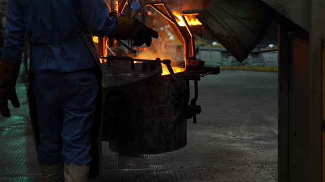 stockvideo's en b-roll-footage met gesmolten metaal smelten, operator werken hard te tikken gesmolten metaal van oven tot pollepel voor gieten naar in gieterij fabriek - crane construction machinery
