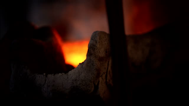 molten metal oozes through a metal shaft from inside a furnace. available in hd. - perdita video stock e b–roll