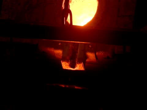 Molten metal poured from cauldron in smelting factory. (sound available)