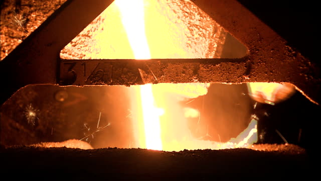 molten metal pours into a container at a foundry. - cast iron stock videos & royalty-free footage