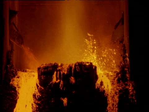Molten metal pours into furnace from chutes at side splashes out and pours down over surface
