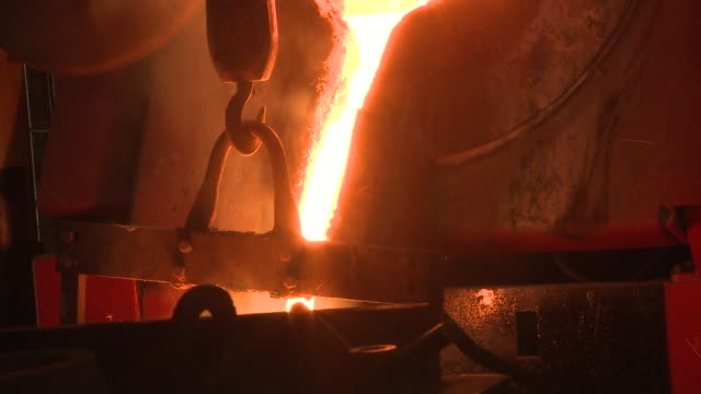 molten steel oozes down a chute into a metal cylinder inside a steel factory. available in hd. - perdita video stock e b–roll