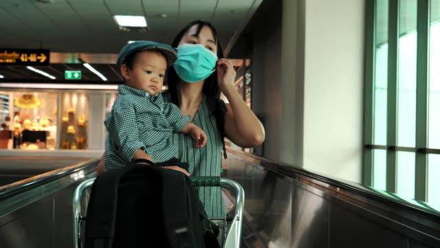 vídeos y material grabado en eventos de stock de mamá y niño usando escaleras mecánicas en el aeropuerto - 6 11 meses