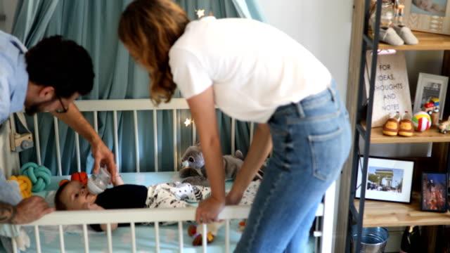 vídeos de stock, filmes e b-roll de mãe e pai alimentando o bebê - quarto de bebê
