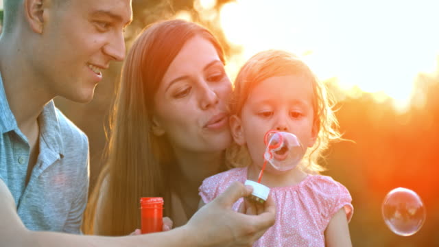 SLO MO Mom and dad helping little toddler daughter blow bubbles at sunset