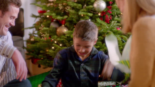 Mom and dad laugh as boy tears into wrapping paper under Christmas tree (dolly-shot)