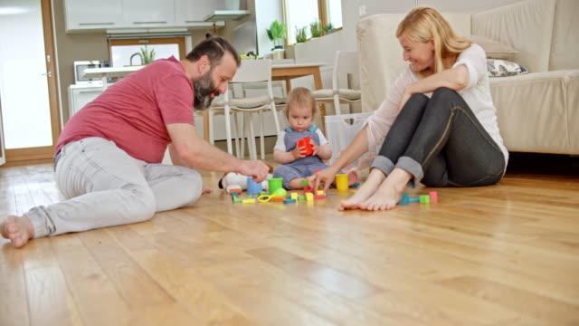 vidéos et rushes de slo mo papa et maman assis sur le sol et en jouant avec leur petit garçon - barefoot