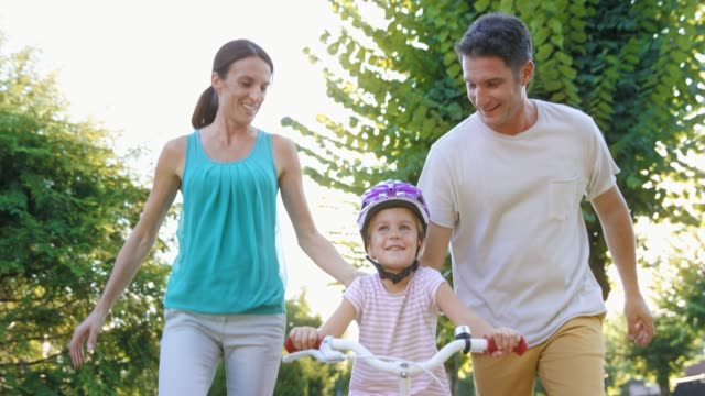slo mo ds mom and dad teaching their little girl ride a bike in sunshine - sports helmet stock videos & royalty-free footage