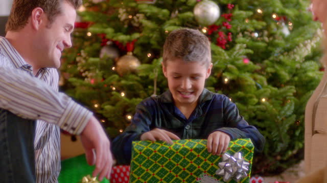 Mom and dad watch as boy carefully unwraps present under Christmas tree (dolly-shot)