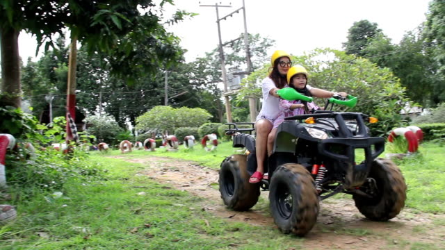 mom and daughter ride atv in soil race by relax time - quadbike stock videos & royalty-free footage