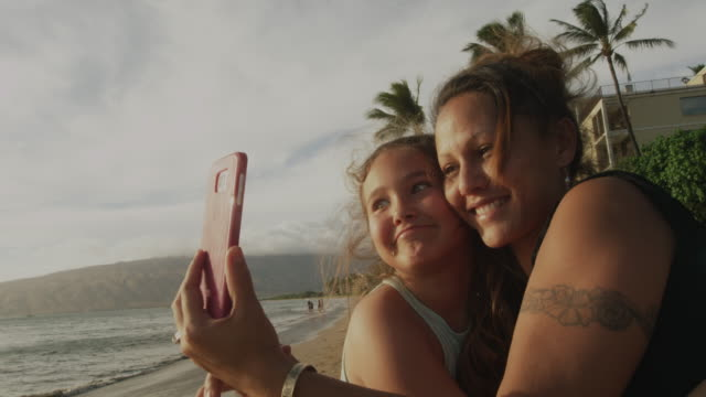 Mom and daughter selfie time on the beach.