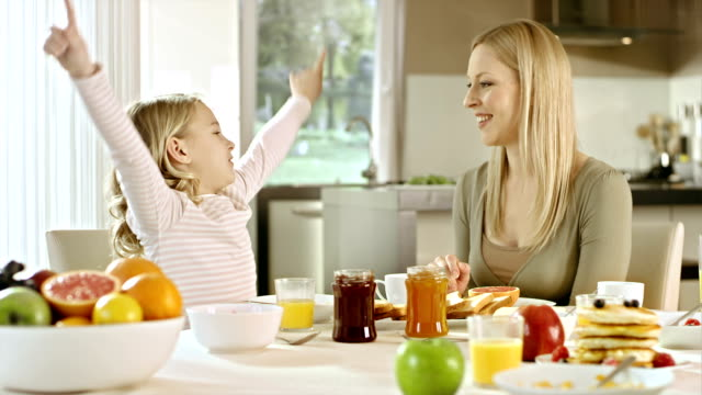Mom and daughter talk at breakfast table