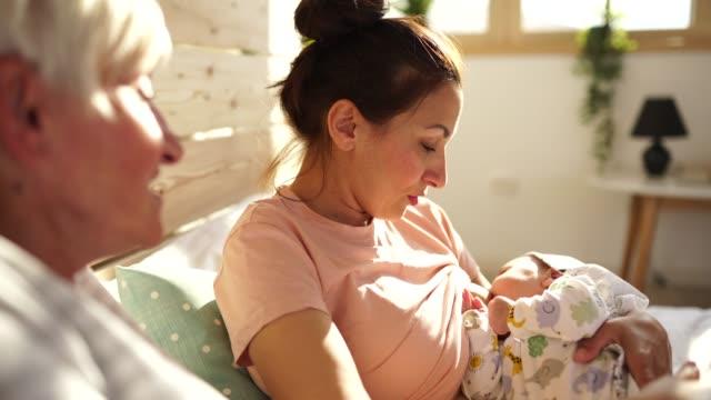 Mama und Tochter sprechen während des Stillens Baby