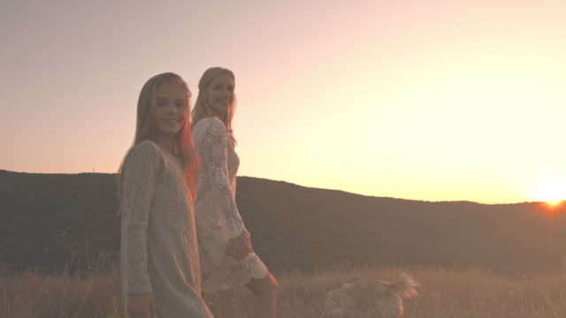 Mutter und Tochter, Wandern mit Hund bei Sonnenuntergang