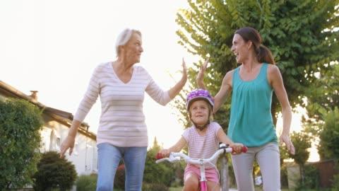 vidéos et rushes de slo mo maman et ma grand-mère faire cinq élevé courir à côté de la petite fille sur son vélo pour la première fois - trois personnes