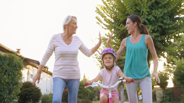slo mo mom and grandma doing high five running next to the little girl riding her bike for the first time - three people stock videos & royalty-free footage