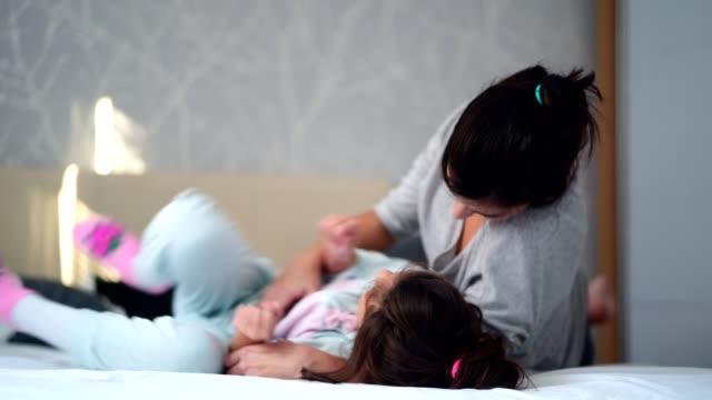 mom and her little girl having fun - fare il solletico video stock e b–roll