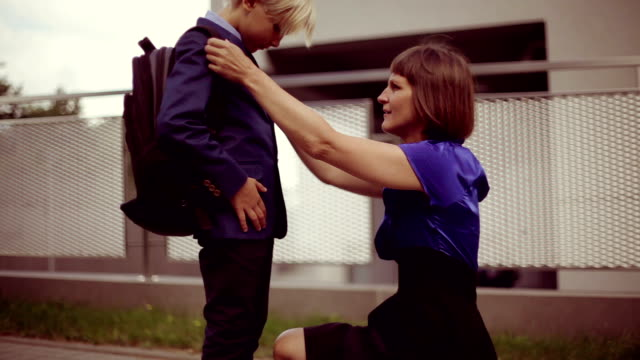 mom and her son (8-9) on goodbye at school fence - zaino da montagna video stock e b–roll