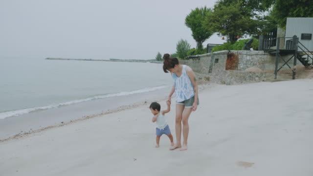 vídeos de stock e filmes b-roll de mom and her son relaxing on the beach - 6 11 meses