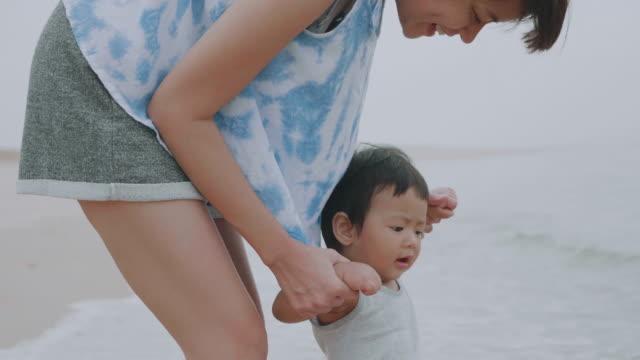 vídeos y material grabado en eventos de stock de mamá y su hijo relajante en la playa - 6 11 meses