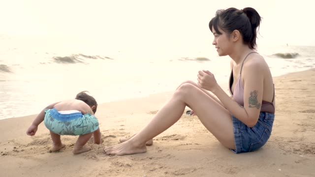 Mom and her son relaxing on the beach.