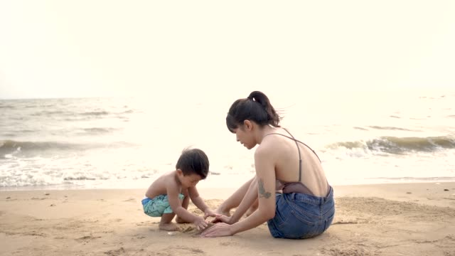 mom and her son relaxing on the beach. - 12 23 months stock videos & royalty-free footage