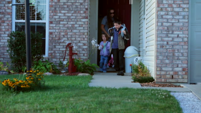 A mom and her two elementary school children leave their house for school in Indianapolis, Indiana.