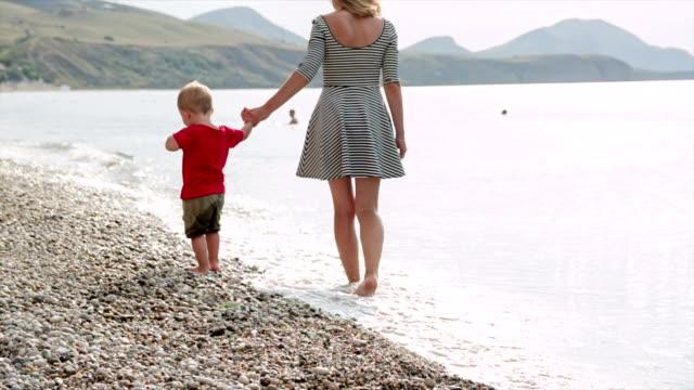 stockvideo's en b-roll-footage met moeder en zoon lopen op het strand - benen gespreid