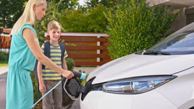 SLO MO Mom and son checking plug on electric car