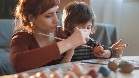 vídeos y material grabado en eventos de stock de mamá y hijo para colorear huevos para pascua - pascua