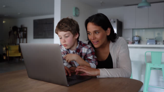 mom and son looking for something online on laptop while mother explains and points at the screen - sitting stock videos & royalty-free footage