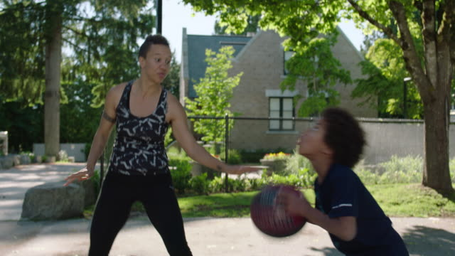 mom and son play one on one basketball on outdoor court - sporting term stock videos & royalty-free footage