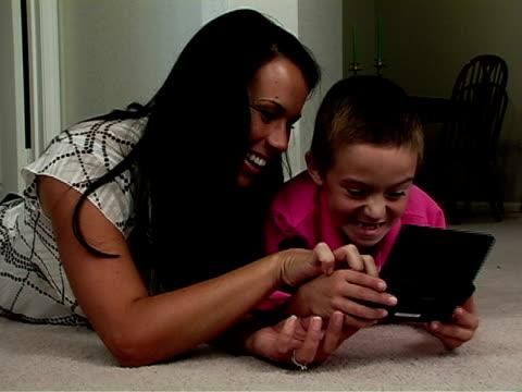 vídeos y material grabado en eventos de stock de madre e hijo juntos - juego electrónico de bolsillo