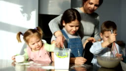 Mom and the kids in the kitchen. Three children knead the dough and play with flour. Joke, fun, learn how to cook when playing