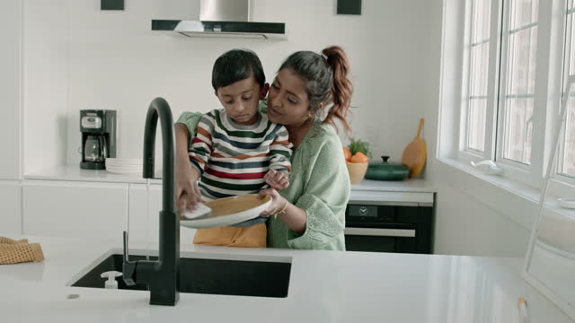 mom and toddler washing dishes together - utensil stock videos & royalty-free footage