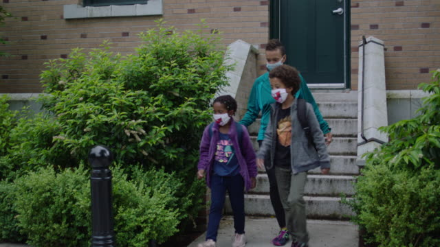 mom and two kids leaving home with masks on - stay at home mother stock videos & royalty-free footage