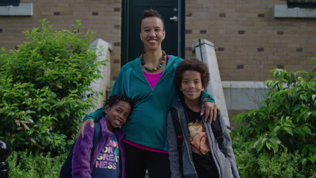 mom and two kids posing out front of their house - front view stock videos & royalty-free footage