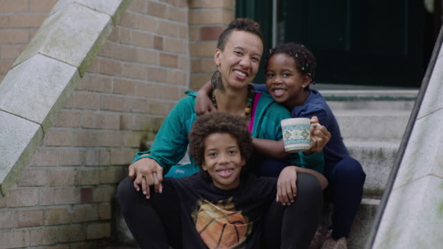 mom and two kids posing out front of their house - community stock videos & royalty-free footage
