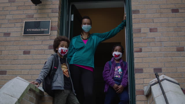 mom and two kids standing outside home with surgical masks on - epidemic stock-videos und b-roll-filmmaterial