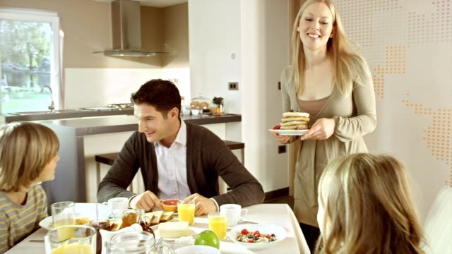 mom bringing pancakes to her family sitting at the table - dining table stock videos & royalty-free footage